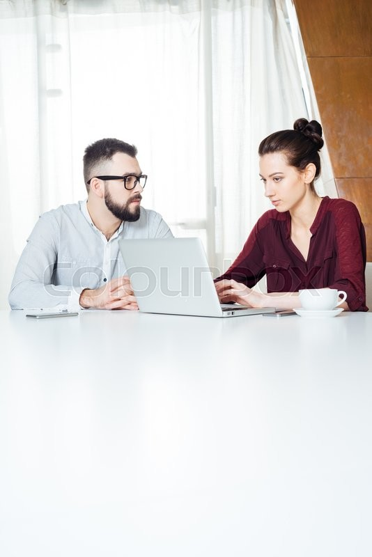 Stock image of 'Two focused young businesspeople sitting and using laptop on the meeting in office'