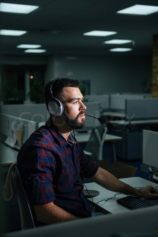 Stock image of 'Serious bearded young businessman in headphones working in office late '