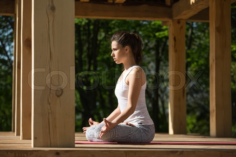 Stock image of 'Young girl is meditate in lotus pose on the wooden terrace on the nature background. She sits on the red yoga mat with her hands on the knees. Her index fingers and thumbs are together. She wears white sleeveless t-shirt and gray pants with patterns. She looks in front of herself. Sunlight falls on her. Photographed from the side. Outdoors. Horizontal.'