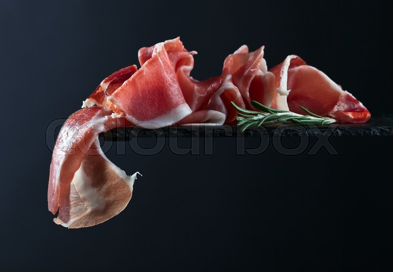Stock image of 'jamon with rosemary on  a black background'