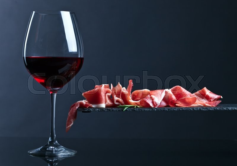 Jamon with red wine on a black background, stock photo