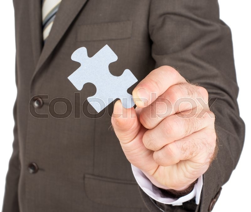 Stock image of 'Close up of businessman hand holding puzzle piece isolated on white background'