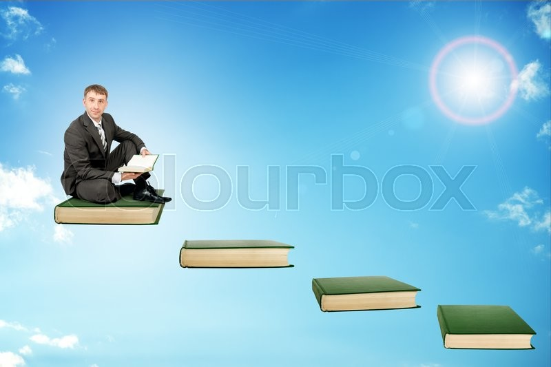 Stock image of 'Young man in sitting on ladder steps with book in hands in sky'