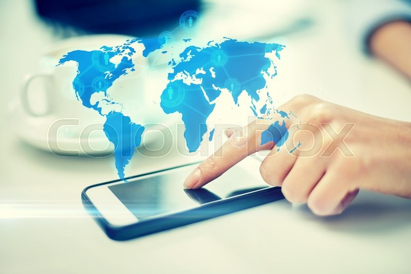 Business, technology, global communication and people concept - close up of woman hand with smartphone and coffee pointing finger to screen over world map projection, stock photo