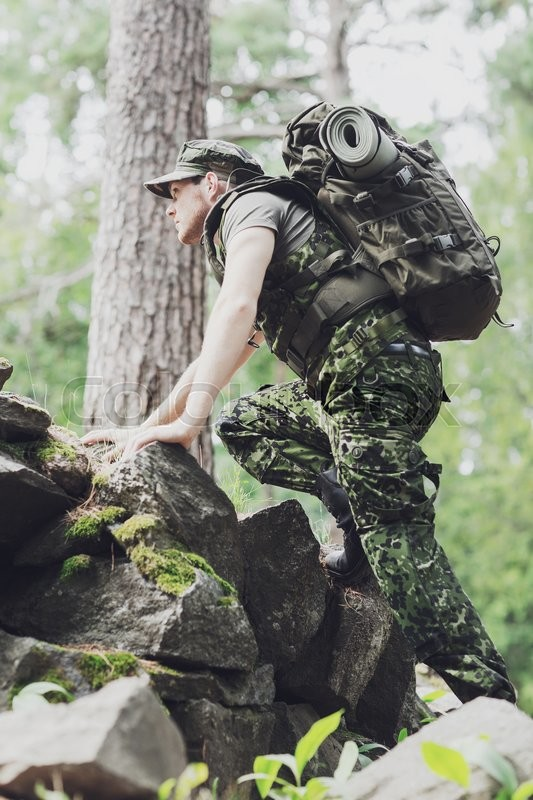 Stock image of 'war, hiking, army and people concept - young soldier or ranger with backpack walking in forest'