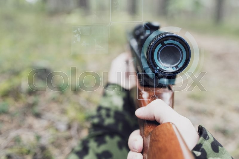 Stock image of 'hunting, war, army, technology and people concept - close up of young soldier or sniper hands holding gun with virtual screen projection and aiming in forest'