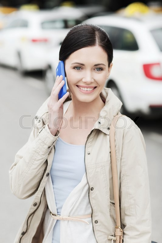 Stock image of 'travel, business trip, people and tourism concept - smiling young woman calling and talking on smartphone over taxi station or city street'