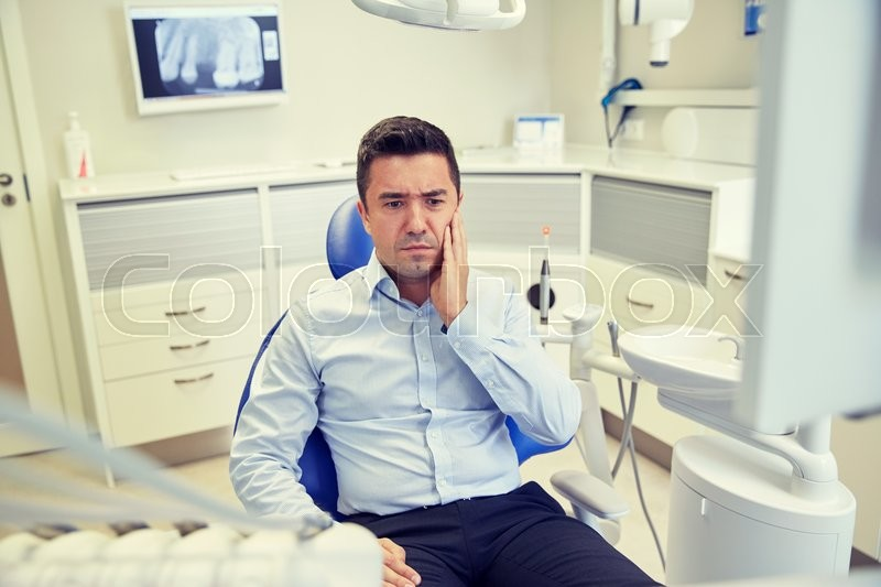 Stock image of 'people, medicine, stomatology and health care concept - unhappy male patient having toothache sitting on dental chair at clinic office'