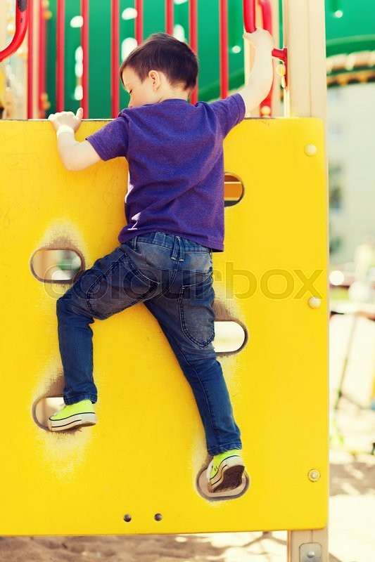 Stock image of 'summer, childhood, leisure and people concept - happy little boy on children playground climbing frame from back'