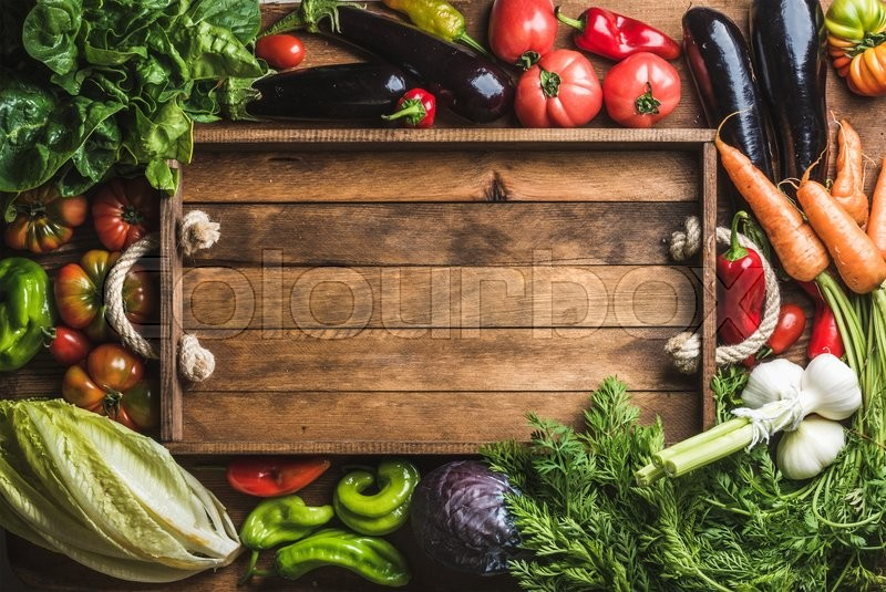 Fresh raw vegetable ingredients for healthy cooking or salad making with rustic wooden tray in center, top view, copy space. Diet or vegetarian food concept, horizontal composition, stock photo