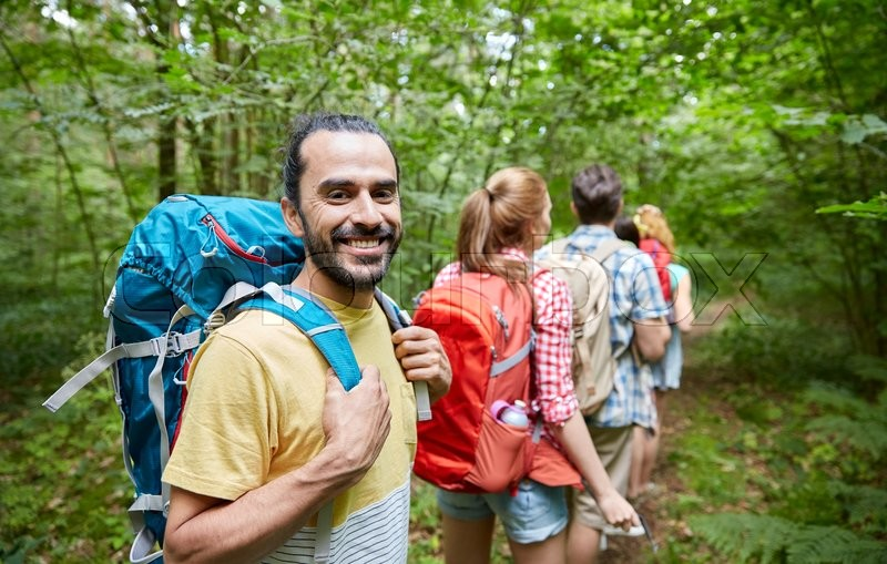 Stock image of 'adventure, travel, tourism, hike and people concept - group of smiling friends walking with backpacks in woods'