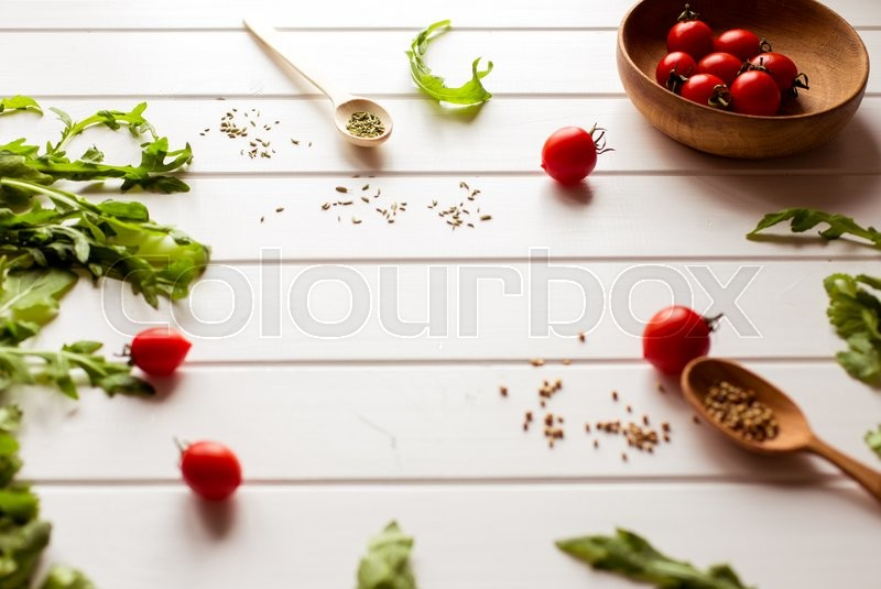 Stock image of 'tomatoes and arugula on a white wooden table'