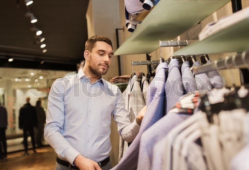 Stock image of 'sale, shopping, fashion, style and people concept - happy young man in shirt choosing jacket in mall or clothing store'