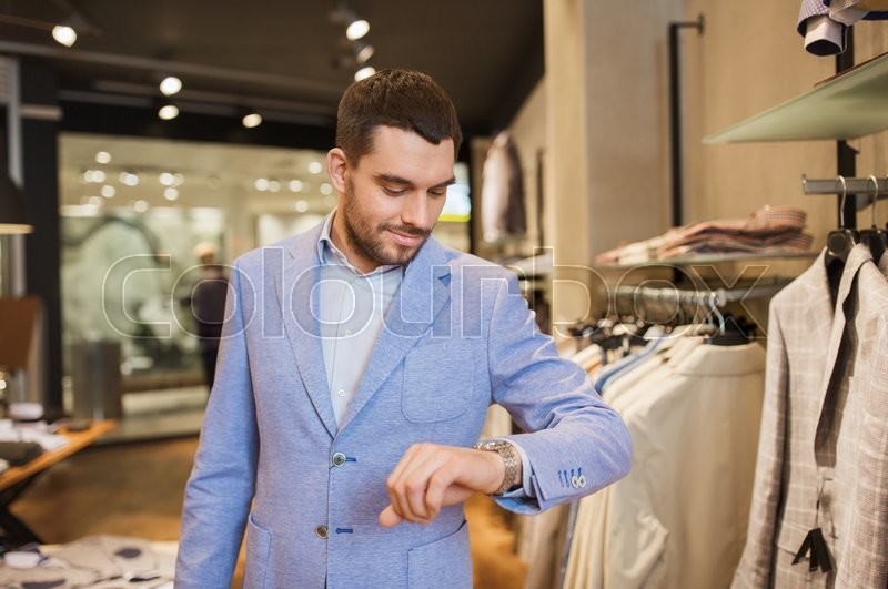 Stock image of 'sale, shopping, fashion, style and people concept - happy young man in jacket looking at wristwatch at clothing store'