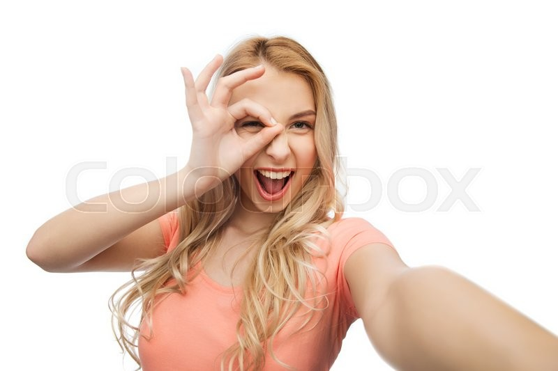 Stock image of 'emotions, expressions and people concept - happy smiling young woman taking selfie'