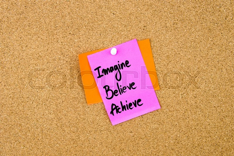 Stock image of 'Imagine Believe Achieve written on paper note pinned on cork board with white thumbtack, copy space available'
