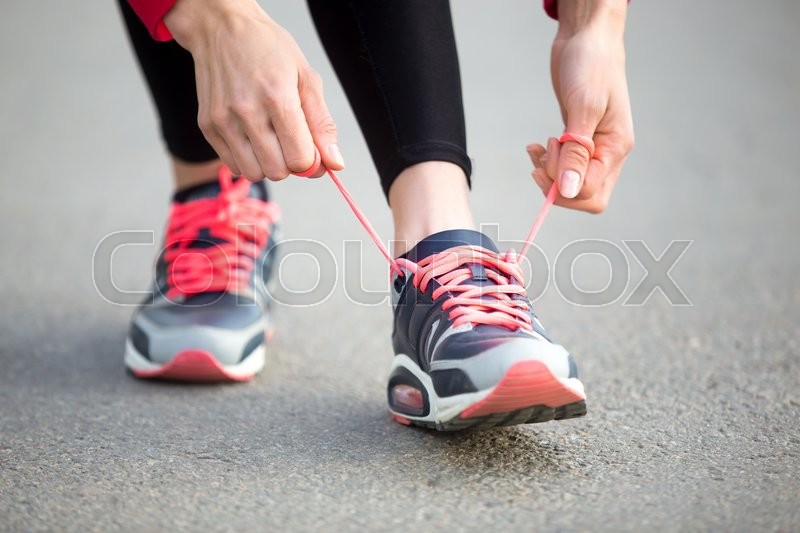 Female hands tying shoelace on running shoes before practice. Woman athlete preparing for jogging outdoors. Runner getting ready for training. Sport active lifestyle concept. Close-up, stock photo