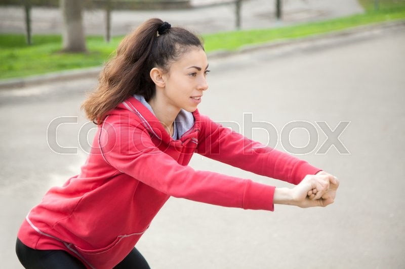 Stock image of 'Portrait of sporty woman doing stretching exercises in park before training. Female athlete preparing for jogging outdoors. Runner doing side lunges. Sport active lifestyle concept. Close-up'