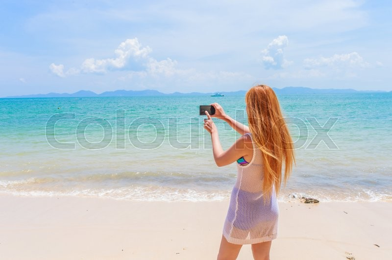 Stock image of 'Happy attractive blonde in bikini taking a self picture on a beautiful sunny beach'