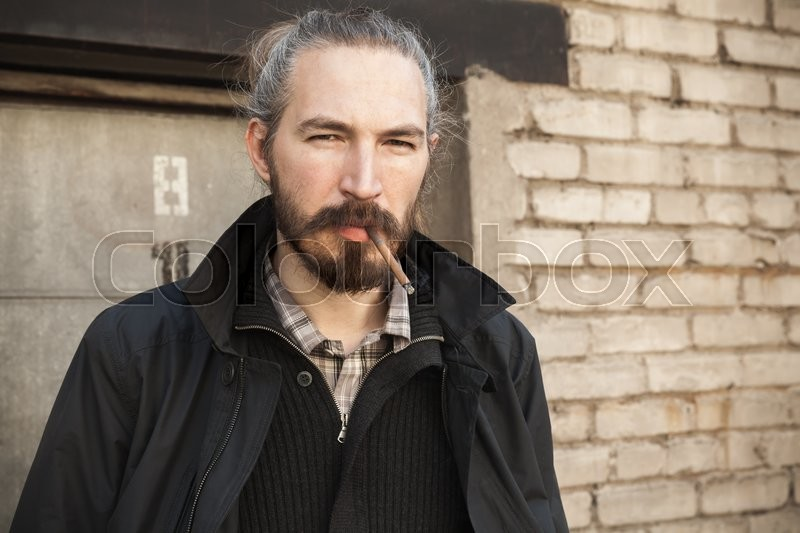 bearded man smoking cigarette over old brick wall outdoor portrait