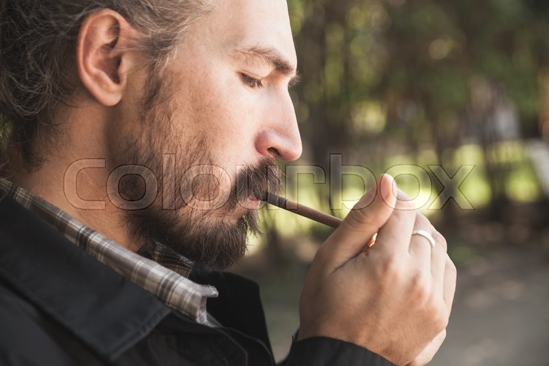 Stock image of 'Bearded Asian man lights a cigarette, outdoor profile portrait with selective focus'