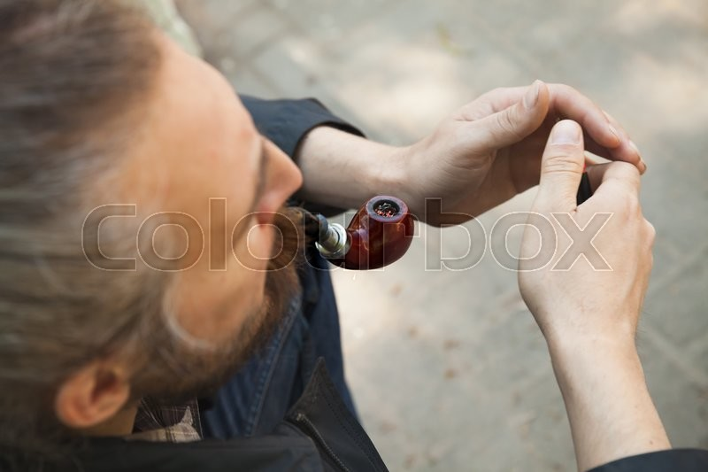 Stock image of 'Man smoking pipe, outdoor photo with selective focus'