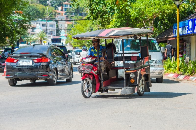 Editorial image of 'KRABI, THAILAND - 12 May 2016: Tourist shuttle public taxi parked on the public roadway along the beach in Ao Nang town.'