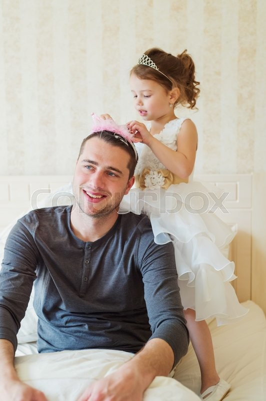 Stock image of 'Cute little girl in princess dress putting pink crown on her father head'