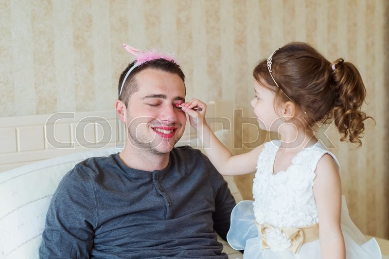 Cute little girl in princess dress putting on colorful make up on her father, stock photo