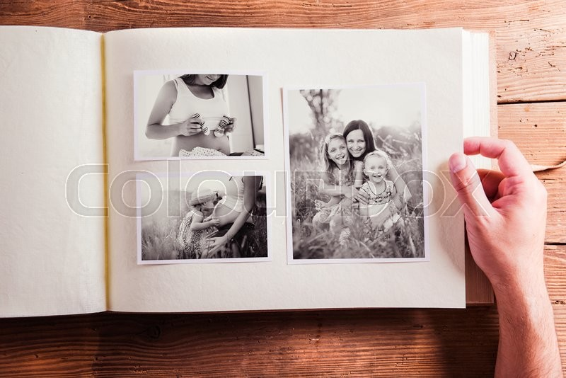Mothers day composition. Hands of unrecognizable man holding a photo album, black-and-white pictures. Studio shot on wooden background, stock photo