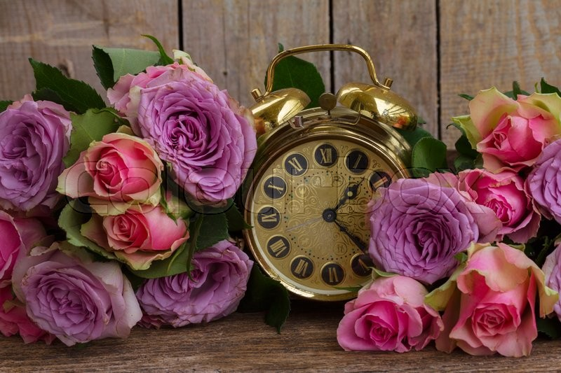 Stock image of 'bouquet of fresh pink and violet  fresh roses with golden vintage clock '