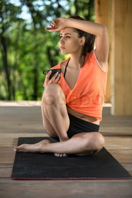 Stock image of 'Young girl sits on the black yoga mat on the wooden terrace on the nature background. Her head is turned to the right, right foot stands on the mat, left leg lies on the mat and right foot, left hand pressed to the head. She holds the black cup in the right hand. She looks to the side. She wears black shorts and orange t-shirt. Outdoors. Vertical.'