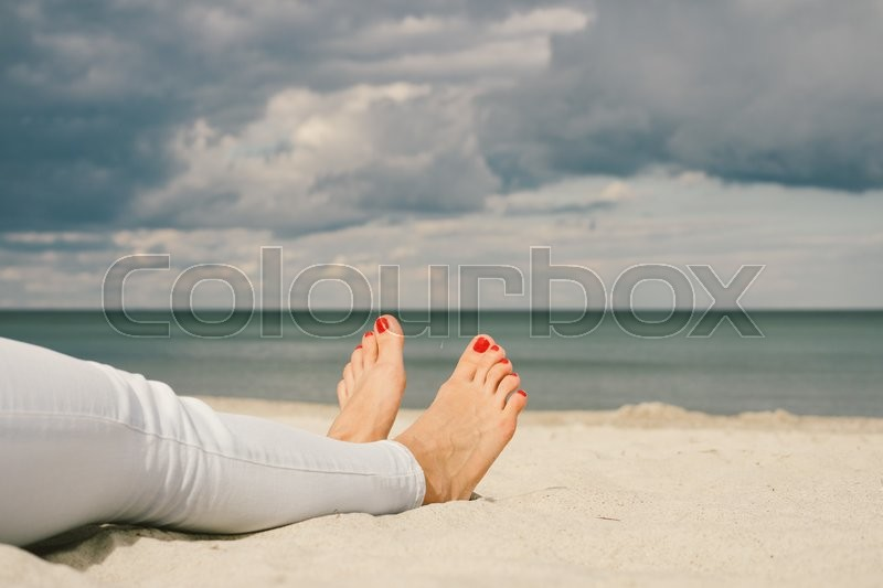 Stock image of 'Female feet on the beach barefoot with red pedicure'