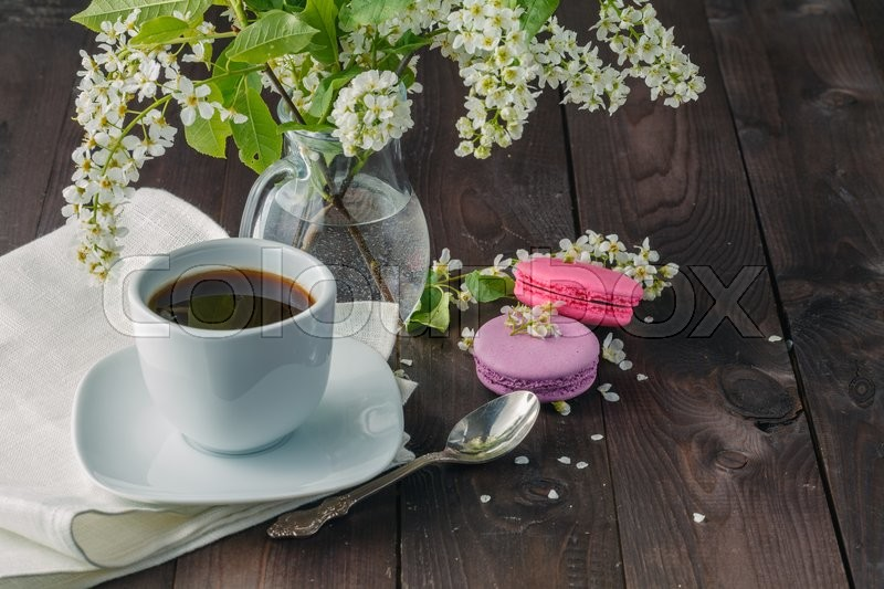 Stock image of 'Spring bouquet in glass mug and tasty macaroons on wooden background'