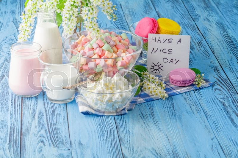 Stock image of 'Glass of milk with Tasty macaroon on with background and message nice day'