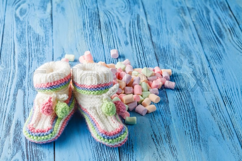 Stock image of 'Baby birthday announcement. Infant booties with sweets'