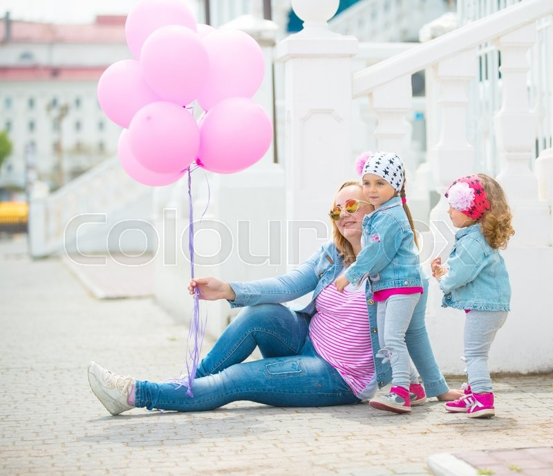 Stock image of 'Happy young family walking along the street of european city with bunch of pink balloons.'