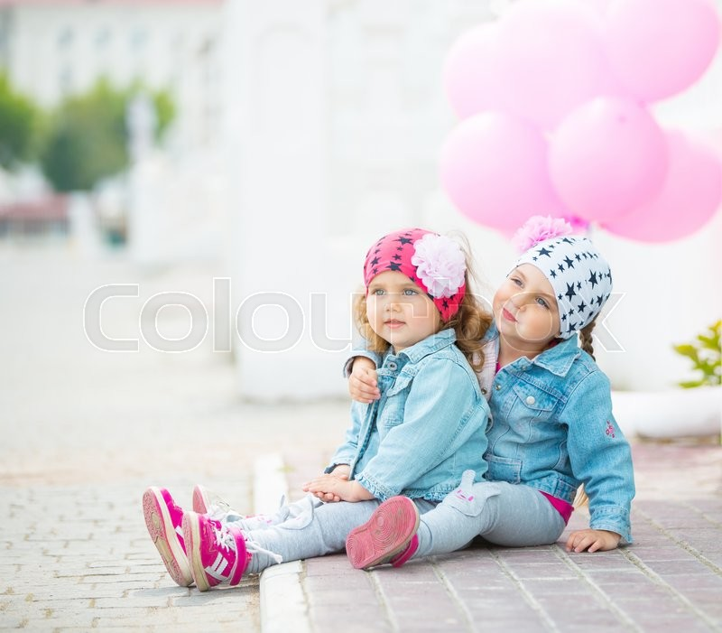 Stock image of 'Happy little girls playing on the street with pink balloons.'
