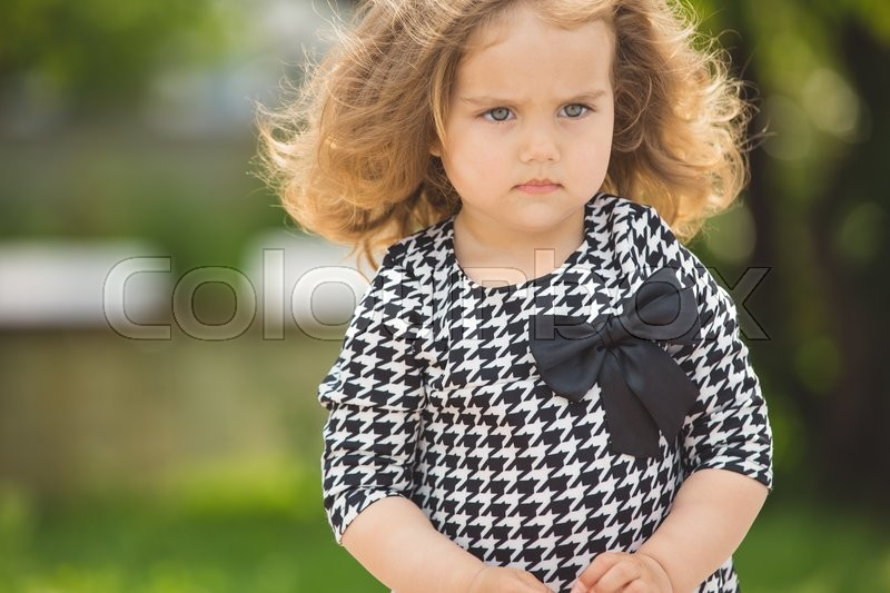 Stock image of 'Little beautiful girl portrait on the summer street'