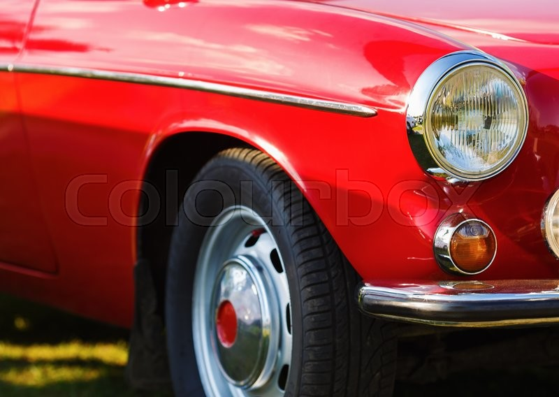 Red vintage car. Close-up fragment of the red vintage car. Headlight of vintage red car. Retro car. Selective focus, stock photo