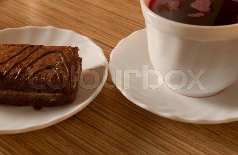 Stock image of 'cake on a white plate standing on the wooden background'