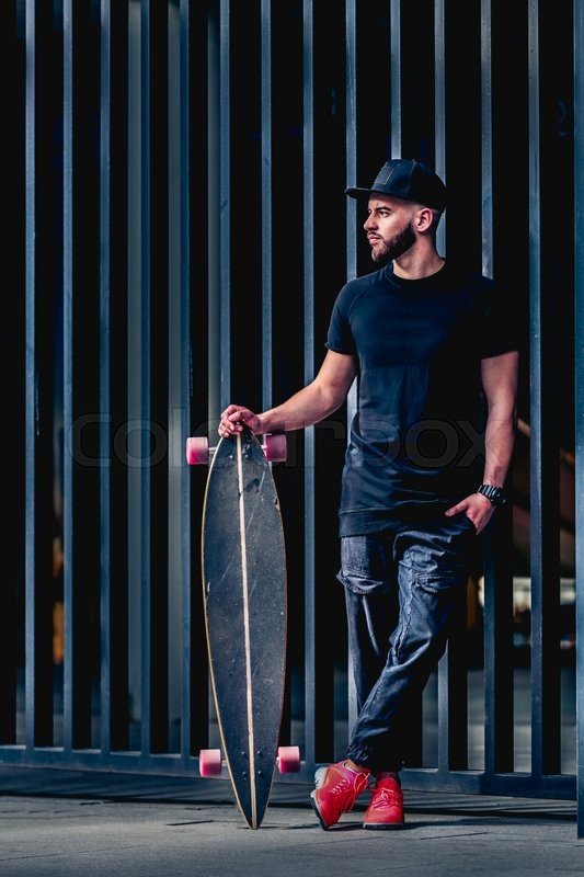 Stock image of 'Full body portrait of bearded stylish man with longboard. Young man with a beard wearing a stylish black clothes. Stylish red sneakers and fashionable cap. Handsome guy posing on metal fence.'