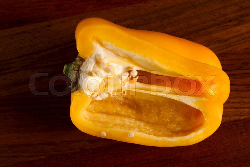 Stock image of 'lying cut on a chopping Board pepper. Visible grains of pepper'