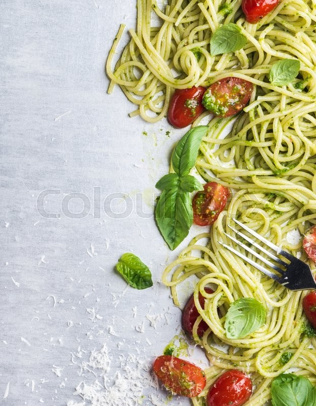 Stock image of 'Spaghetti with pesto sauce, roasted cherry-tomatoes, fresh basil and parmesan cheese on steel backdrop. Top view, copy space'