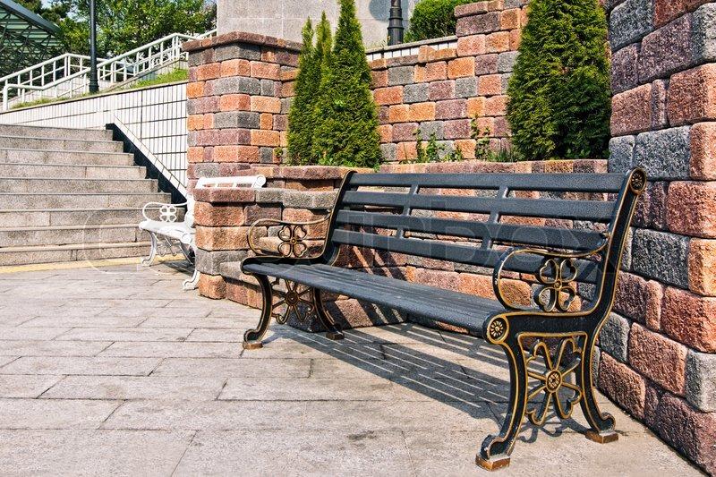 metalic bank in einem stadtpark in der umgebung der kleinen thuja b umen und mauerwerk. Black Bedroom Furniture Sets. Home Design Ideas