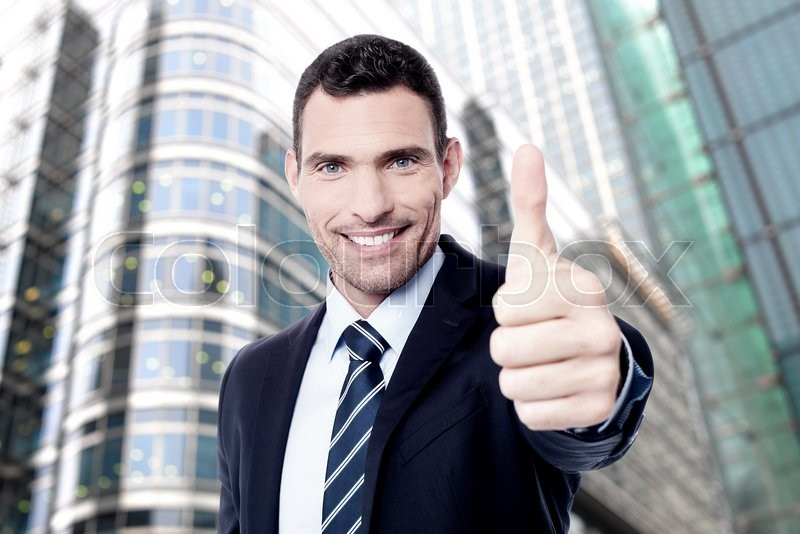 Stock image of 'Businessman showing OK sign with his thumb up'