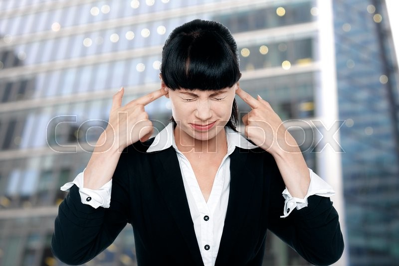 Stock image of 'Irritated businesswoman closing her ears with fingers'