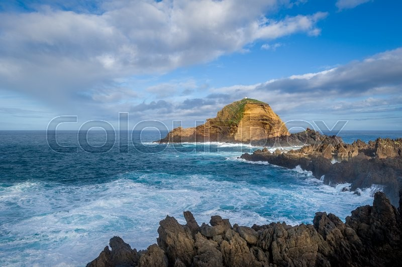 Stock image of 'Atlantic sea, volcanic lava rocks and small rocky island with lighthouse on the cliff. Scenic views of Madeira north coast.'