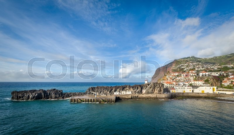Stock image of 'Panoramic view of Camara de Lobos fishing village harbor. Old town buildings, pier and small lighthouse on the rocky shore of Atlantic ocean. Madeira island, Portugal.'