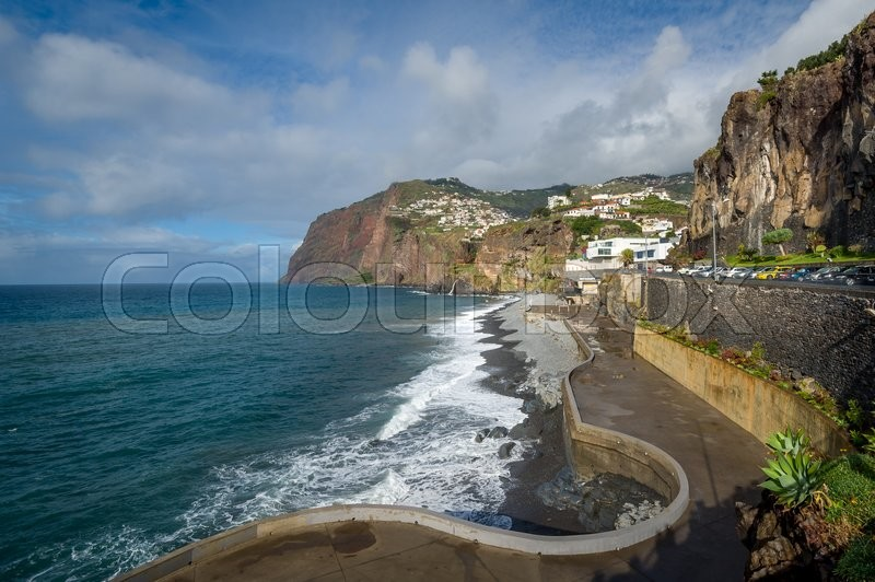 Stock image of 'Long Madeiran embankment view and villages on the mountains. Rocky shores of Madeira island south coast. Walking route near Camara de Lobos town.'